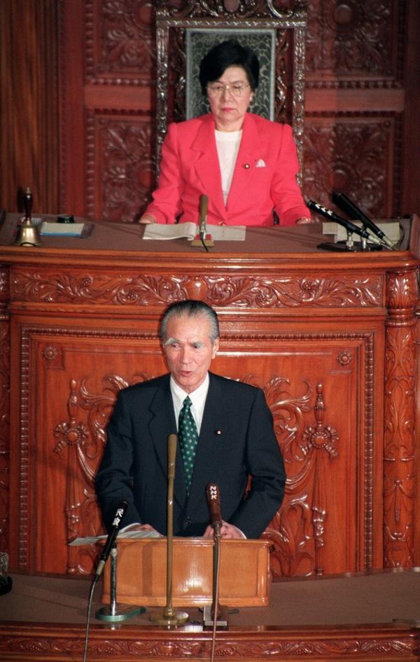 Takako Doi sitzt vor einem Redner, der an einem Redepult steht